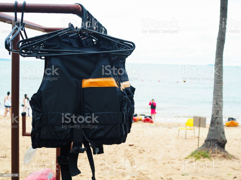 The row of life jacket or life vest hang on a metal bar. stock photo
