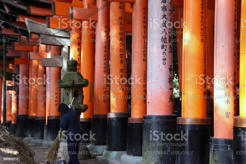 The row of torii and stone lantern with sweeper at Japanese shrine. stock photo