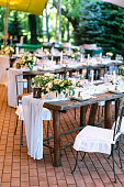 The rows of beautifully served wooden festive tables are arranged in a clear order, covered with natural fabric tablecloths, decorated with flower bouquets and filled with glasses and utensils.