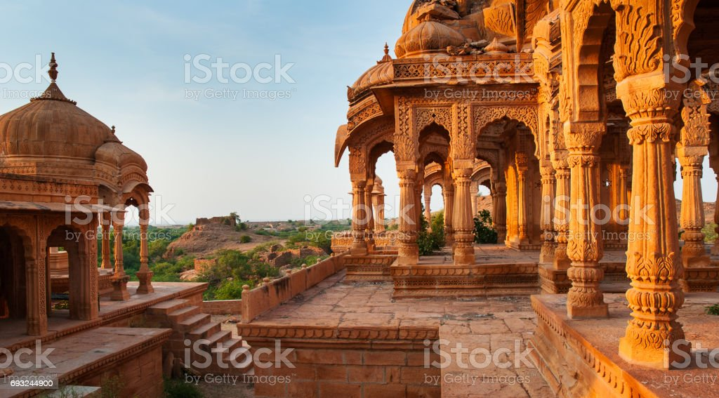 The royal cenotaphs of historic rulers, also known as Jaisalmer Chhatris, at Bada Bagh in Jaisalmer, Rajasthan, India. Cenotaphs made of yellow sandstone at sunset stock photo