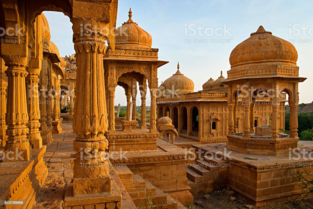 The royal cenotaphs of historic rulers, also known as Jaisalmer Chhatris, at Bada Bagh in Jaisalmer made of yellow sandstone at sunset stock photo