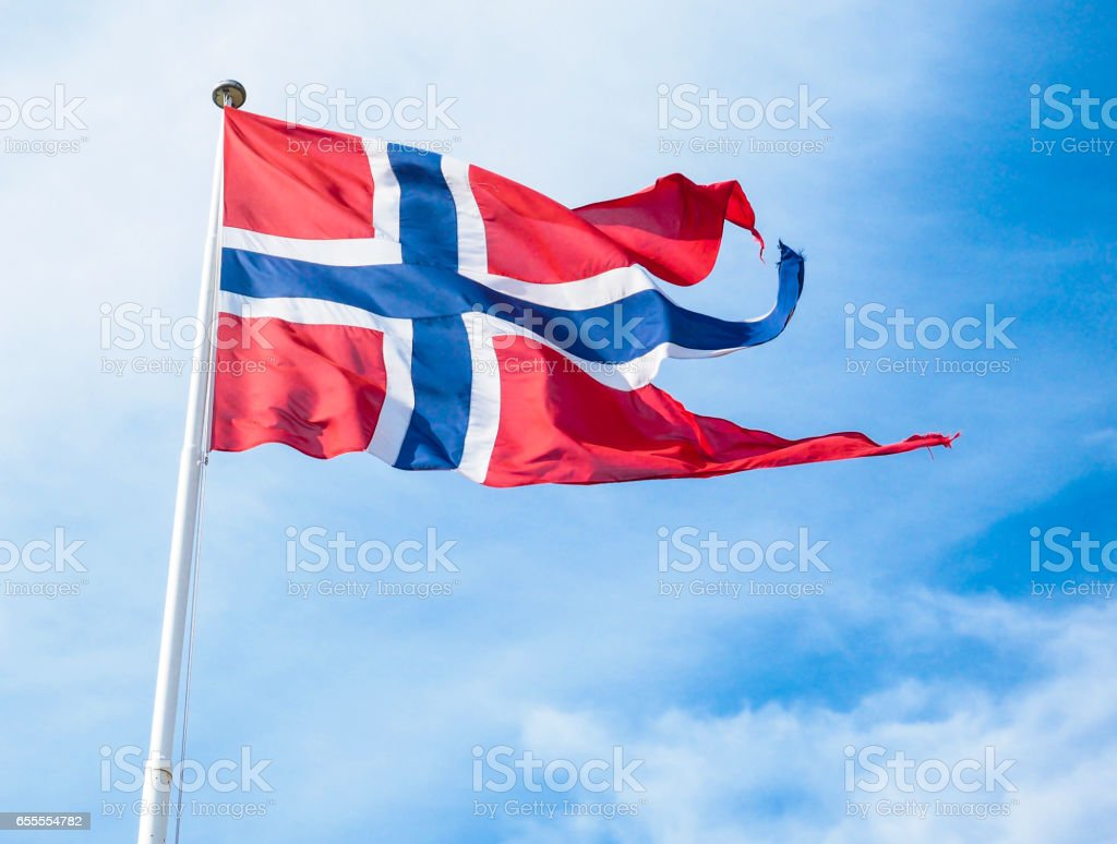 The Royal flag of Norway on a pole towards blue and white sky in daylight - fotografia de stock