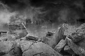 istock The ruins of concrete and brick rubble in front of the large city building are covered with smoke from the civil war and the city abandonment, concept of war 1277561091
