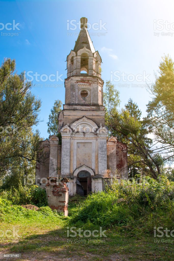 The ruins of old Christian Church on a background of bright trees and a blue sky stock photo