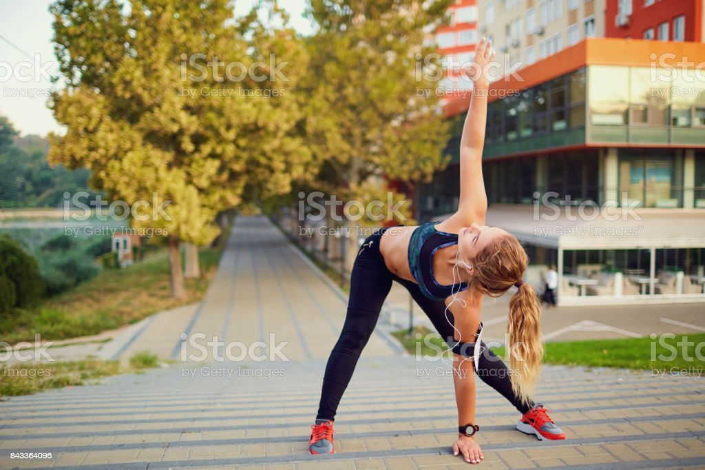 The runner girl does the warm-up before jogging in the park in t stock photo