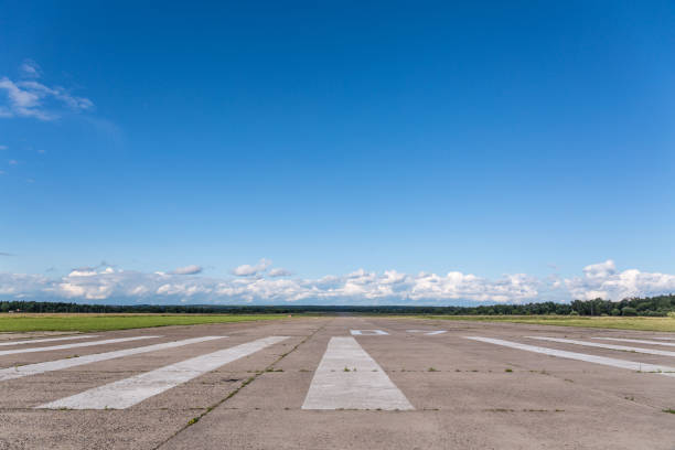 de landingsbaan van een landelijk klein vliegveld tegen een blauwe hemel - vliegveld stockfoto's en -beelden