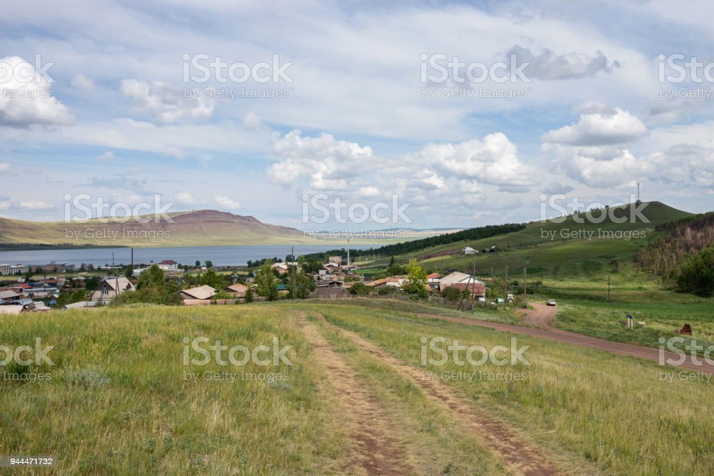 The rural dirt road leads to the settlement  'Lake Uchum' on the shore of the lake. stock photo