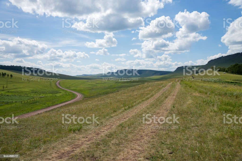 The rural road goes along the mountain ridge on the background of the green steppe. stock photo