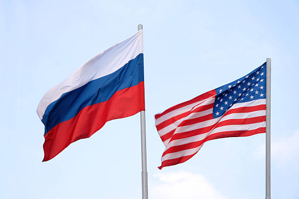the russian and american flags flying side by side - russia stock pictures, royalty-free photos & images