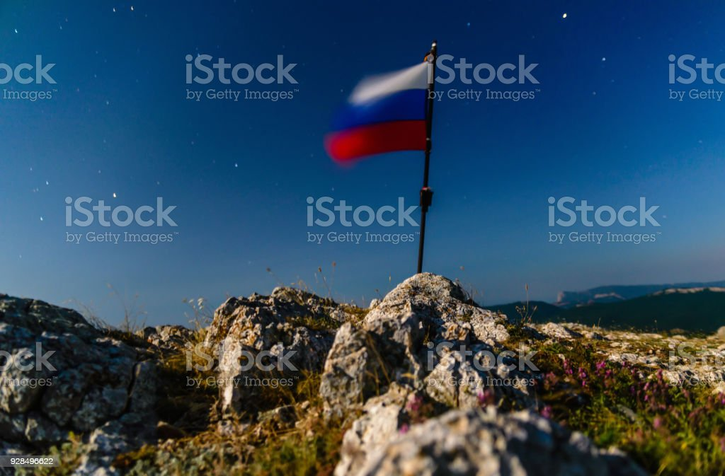 The Russian flag at the top of the mountain stock photo