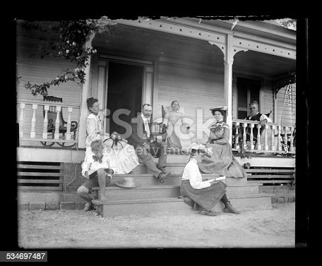 Beautiful Black and White portrait of a family on the front porch of a Farmhouse on a Sunday afternoon wearing Victorian-era clothing. The picture includes grandparents, parents, and Aunt, and children. Everyone is dressed up in their church clothes. The image was digitally restored from a glass plate taken circa 1890.