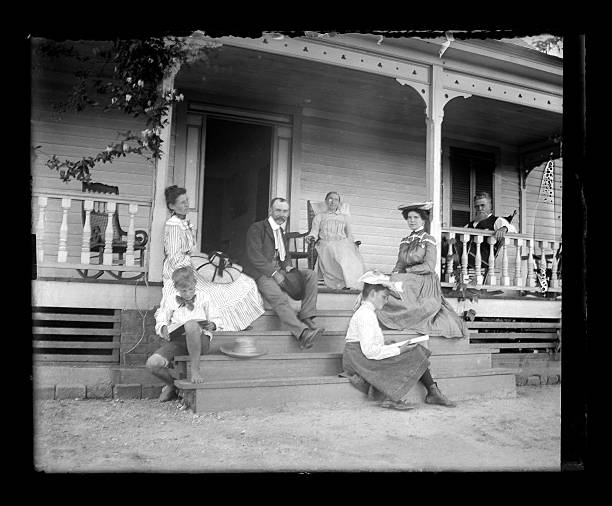 The Sabbath Beautiful Black and White portrait of a family on the front porch of a Farmhouse on a Sunday afternoon wearing Victorian-era clothing. The picture includes grandparents, parents, and Aunt, and children. Everyone is dressed up in their church clothes. The image was digitally restored from a glass plate taken circa 1890. 1890 stock pictures, royalty-free photos & images