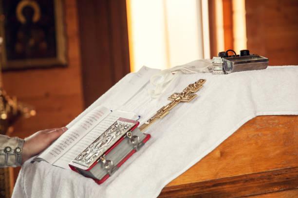 das sakrament der taufe in der orthodoxen kirche. gebetsbücher und ein kruzifix auf dem tisch - achtsamkeit persönlichkeitseigenschaft stock-fotos und bilder