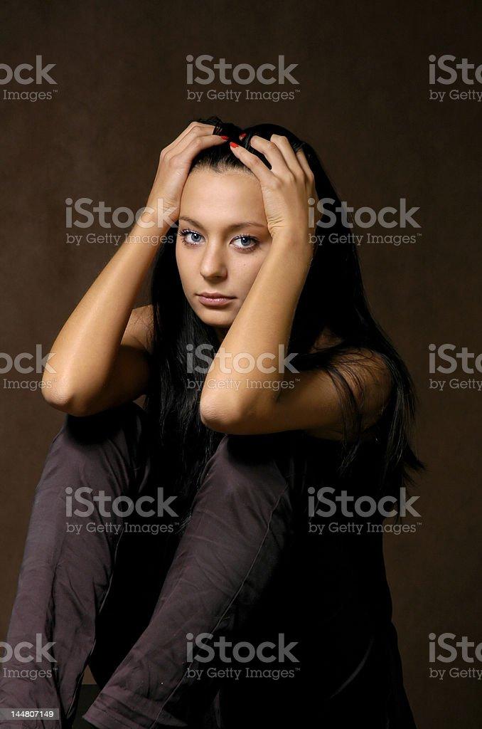 The sad beautiful girl on a dark background royalty-free stock photo
