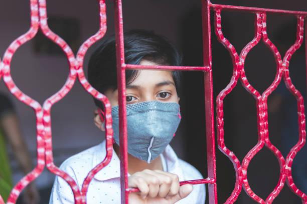 der traurige junge schützt sich und trägt eine maske gegen das corona-virus - standbildaufnahme stock-fotos und bilder