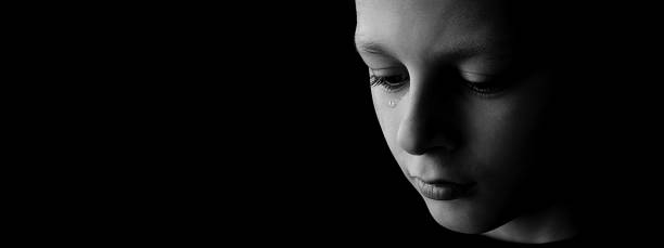 der traurige junge mit tränen in den augen auf schwarzem hintergrund - träne stock-fotos und bilder