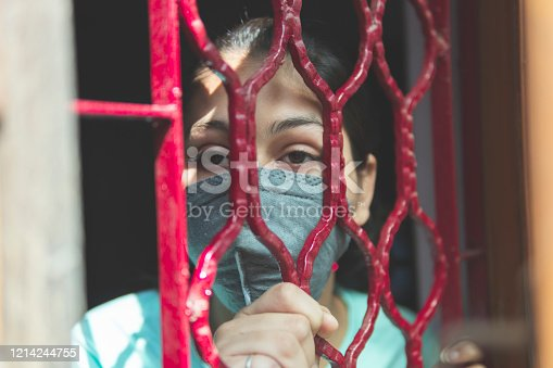 Indian girl is protecting herself and wearing a mask against the corona virus and following public curfew. indoor shoot at home. copy space. people fighting against covid-19. concept shoot. dangerous viruses.