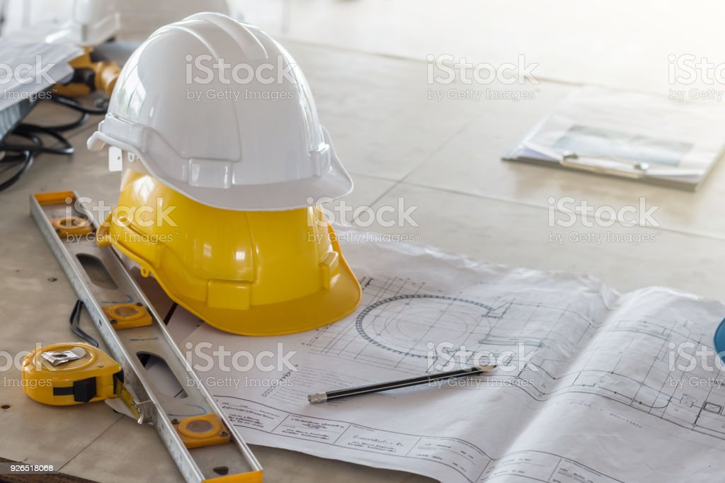 Der Helm Und Die Blaupause Auf Tisch Auf Baustelle Stock Fotografie