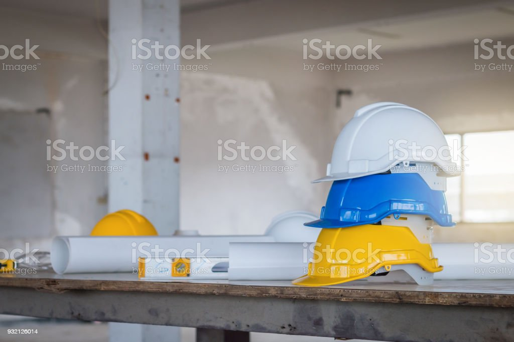 The safety helmet and the blueprint on table at construction site stock photo