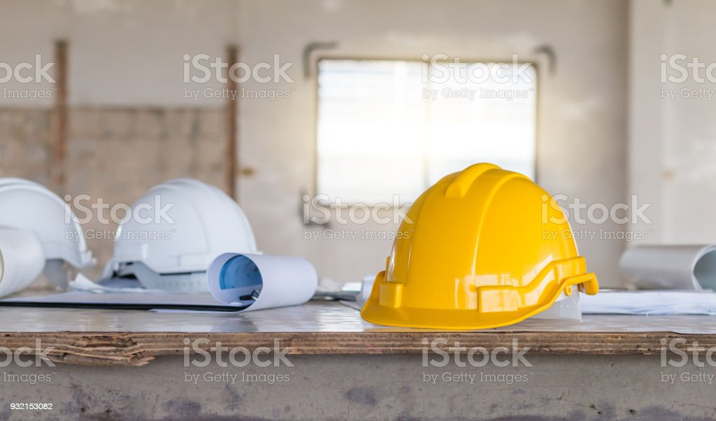 The safety helmet and the blueprint on table at construction site the safety helmet and the blueprint on table at construction site royalty free stock photo malvernweather Images
