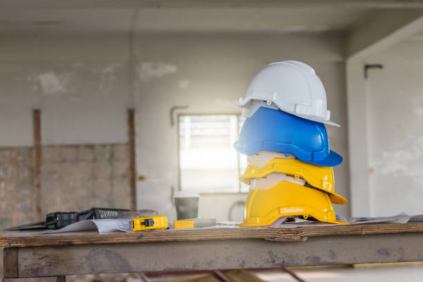 Royalty free white drawing paper on blue planks or table top the safety helmet and the blueprint on table at construction site stock photo malvernweather Images