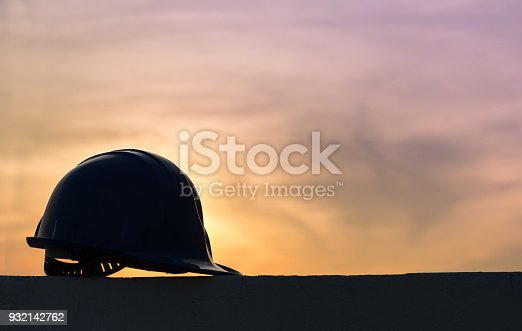istock The safety helmet silhouette at construction site with sunset background 932142762