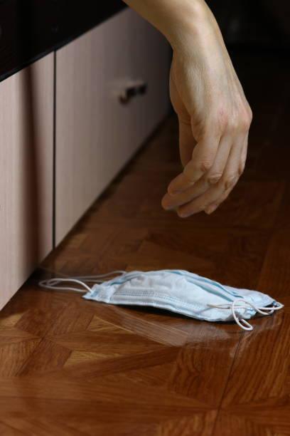 床に医療用マスクを持つ病気の人のたるみ手 ストックフォト
