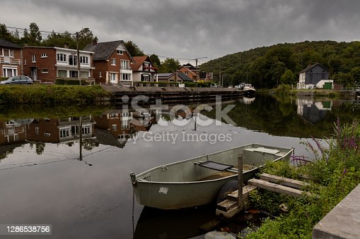 A boat on the water and the city of Thuin reflected in the river Samber