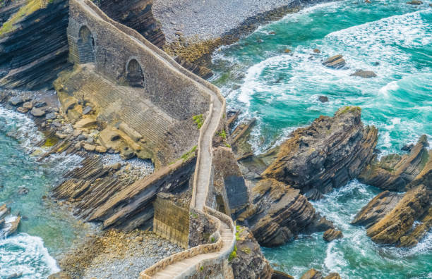 The San Juan de Gaztelugatxe hermitage on an islet on the Bay of Biscay, Basque Country, Spain. Gaztelugatxe, an islet on the coast of the Bay of Biscay, Bermeo, Basque Country, Northern Spain. It is connected to the mainland by a man-made stone bridge. On top of the island stands a hermitage (San Juan de Gaztelugatxe), dedicated to John the Baptist from the 9th and 10th century. With another small neighboring island, Aketx, they form a protected biotope that extends from the town of Bakio until Cape Matxitxako, on the Bay of Biscay. santander spain stock pictures, royalty-free photos & images