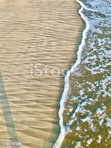 Geometric forms in the sand and wave in Acapulco beach