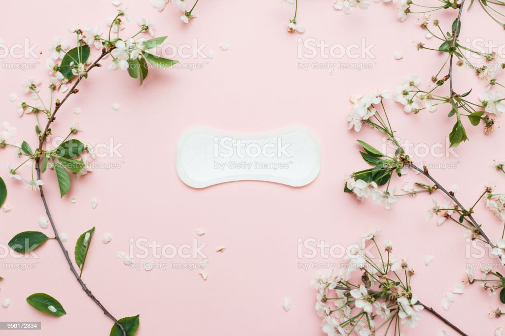The sanitary napkin lying with blossom on pink background. stock photo