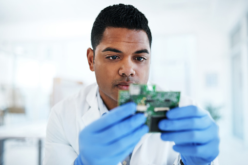 Shot of a young man repairing computer hardware in a laboratory