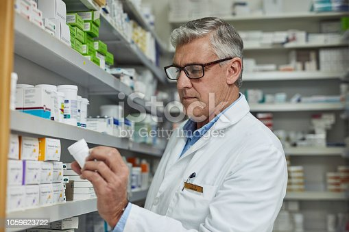 Shot of a mature pharmacist reading the label on a box of medicine in a pharmacy