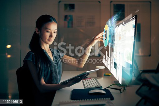 Shot of a young programmer using a digital tablet and computer at night in a modern office
