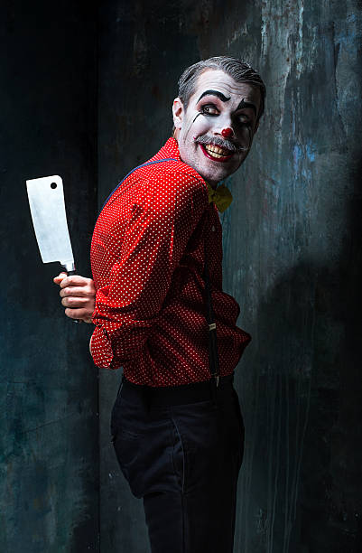 the scary clown holding a knife on dack. halloween concept - horror zirkus stock-fotos und bilder