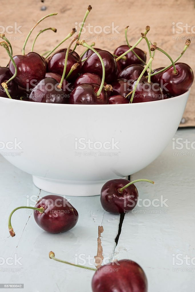 The scattered cherries in a white bowl – zdjęcie