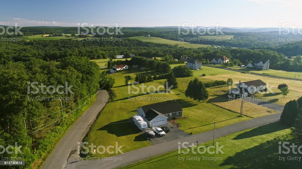 The scenery aerial view of Poconos, Monroe County, Pennsylvania. The sunny summer morning. The panoramic overview over the field and forest to the Kunkletown, then to the small farm near by the road. stock photo