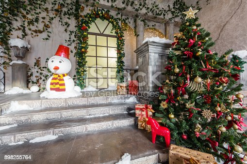 the scenery of the Studio or theater. Entrance in an old architecture with staircase and columns. Christmas decoration with garlands and fir branches.