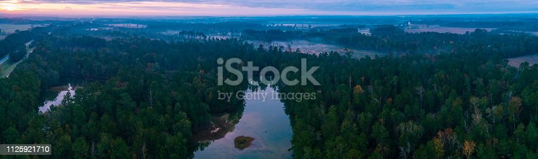 The scenic aerial panoramic view of the foggy swamps, forest, and river in nearby Hardeeville, South Carolina, USA at early morning in November