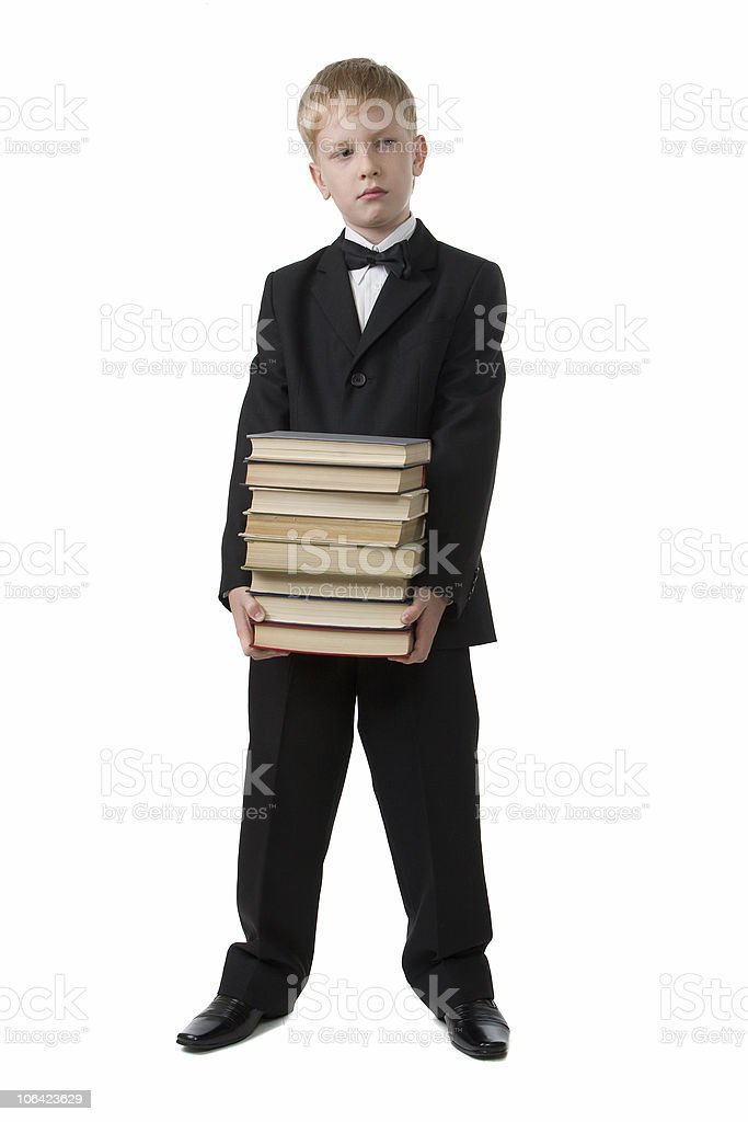 The schoolboy holds a pile of books. stock photo