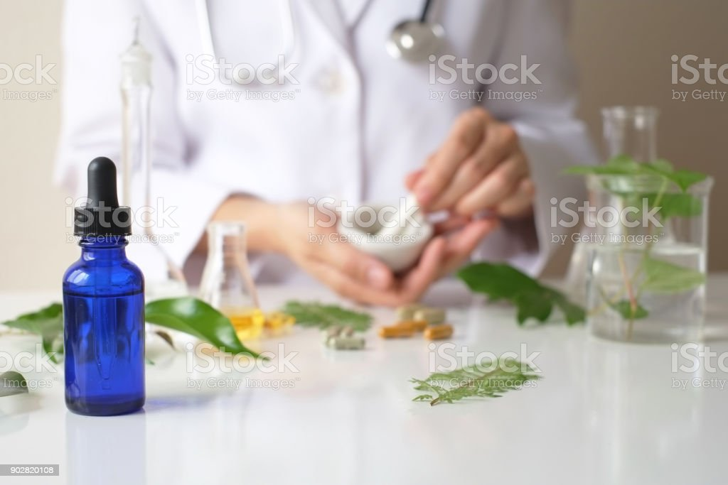 the scientist or doctor make herbal medicine from herb in the laboratory on the table .alternative treatment. show hand and stethoscope. with the bottle container. royalty-free stock photo