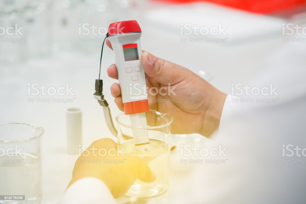 The scientist work at the chemical solution with handle pH meter in the laboratory stock photo