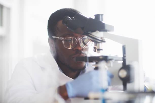 Der Wissenschaftler arbeitet mit einem Mikroskop in einem Labor, die Durchführung von Experimenten und Formeln. – Foto