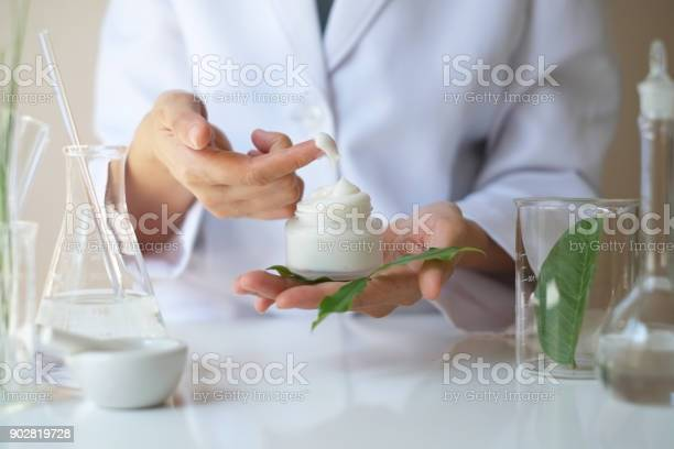 the scientist,dermatologist testing the organic natural product in the laboratory.research and development beauty skincare concept.blank package,bottle,container .cream,serum.