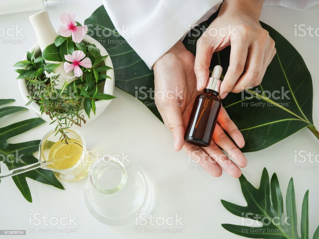 the scientist,dermatologist with the organic natural product in the laboratory.research and development beauty skincare concept.blank package,bottle,container .cream,serum.hand stock photo