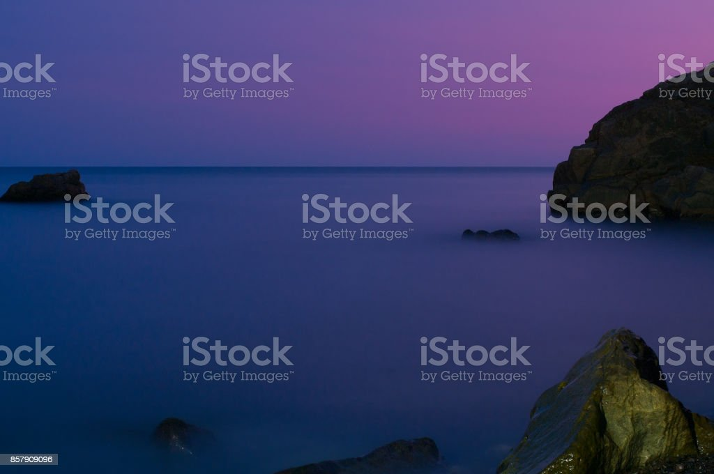 The sea and the stones after sunset stock photo