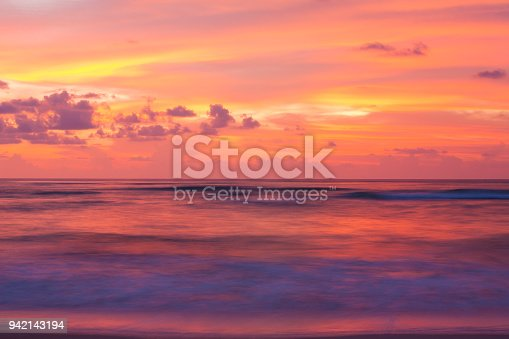 The sea is calm under the last light of day, fantastic clouds and sunset sky. Slow-shutter photography. Takua Pa District, Phang Nga Province, Andaman Sea, Thailand.