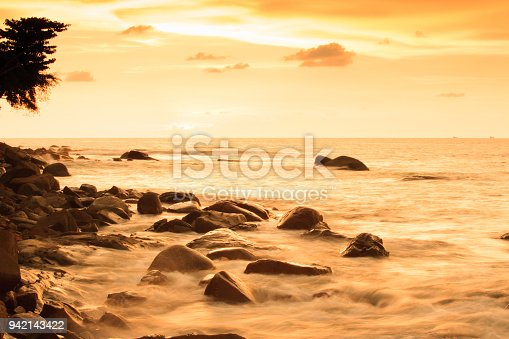 The sea is calm under the last light of day, fantastic sunset sky. Slow-shutter photography. Khao Lak Beach, Phang Nga Province, Andaman Sea, Thailand.