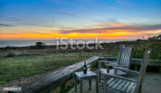 The Sea Ranch, Sunset on deck with wine and wine glasses by rocking chairs