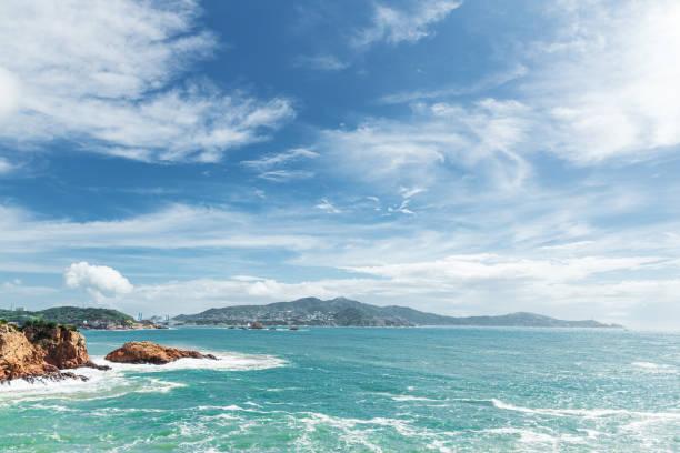 El mar bajo el cielo azul y las nubes blancas - foto de stock